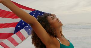 Front view of African American woman with waving American flag dancing on the beach 4k. Front view of African American woman with waving American flag dancing on stock footage