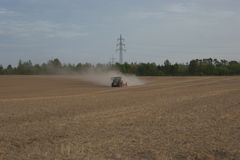Front view of an agricultural tractor harrowing a field during the summer drought of 2018 in Germany. While plowing a field the tractor is pulling a large dust Royalty Free Stock Photo