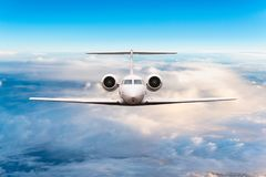 Front view of aircraft. Privat jet in flight. The passenger plane flies high above the clouds and blue sky. Luxury. Travel concept stock image
