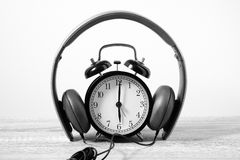 Front View Alarm Clock put on headphones over Wooden Table. Time Royalty Free Stock Image
