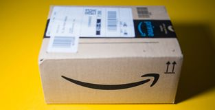 Front view Amazon Prime cardboard box tilt-shift. PARIS, FRANCE - SEP 28, 2018: Front view of new Amazon Cardboard box against yellow background smile log- tilt royalty free stock photo