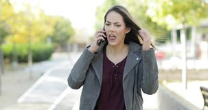 Angry woman arguing on phone in a park. Front view of an angry woman arguing on phone walking in a park stock video