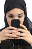 Front view of an arab woman addicted to the smart phone. Isolated on a white background Royalty Free Stock Image