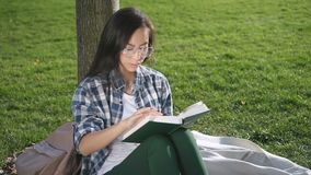 Front view of Asian American woman reading book, sitting outdoors. Female student in eyewear having enjoying time, relaxed in good mood. 20s person is in stock video footage