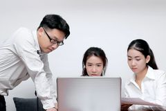 Front view of Asian business people with laptop working together in modern office. Selective focus and shallow depth of field. Front view of Asian business Royalty Free Stock Image