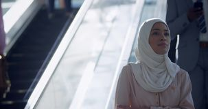 Businesswoman in hijab using escalator in a modern office 4k. Front view of Asian Businesswoman in hijab using escalator in a modern office. She is looking away stock footage
