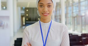 Asian businesswoman standing in the lobby at office 4k. Front view of an Asian businesswoman standing and smiling while looking at the camera in the office lobby stock footage