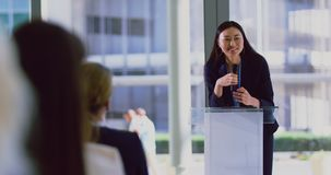 Female speaker speaks in a business seminar at modern office 4k. Front view of asian female speaker speaks in a business seminar at modern office. Business stock video