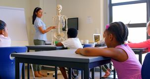 Asian female teacher explaining about skeleton model in classroom 4k. Front view of Asian female teacher explaining about skeleton model in classroom. They are stock video footage