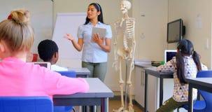 Asian female teacher explaining about skeleton model in classroom 4k. Front view of Asian female teacher explaining about skeleton model in classroom. She is stock video