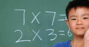 Front view of Asian schoolboy standing against chalkboard and showing chalk in classroom 4k. Front view of Asian schoolboy standing against chalkboard and stock video