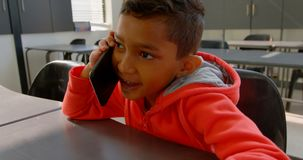 Front view of Asian schoolboy talking on mobile phone at desk in classroom at school 4k. Front view of Asian schoolboy talking on mobile phone at desk in stock footage