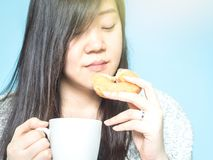 Front view from asian woman hand with cloth hold the white coffe. E cup and eat donut on morning time with blue pastel background Royalty Free Stock Photo