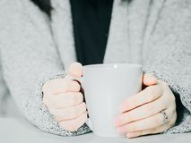 Front view from asian woman hand with cloth hold the white hot c. Offee cup from hand warming and drink on morning time with soft focus background Stock Photo