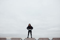 Front view of athlete after exercising standing on stone proudly and contentedly. Royalty Free Stock Image