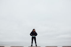 Front view of athlete after exercising standing on stone proudly and contentedly. Stock Photo