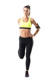 Front view of athletic young pretty woman jogger stretching leg muscles exercise Royalty Free Stock Image