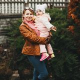 Attractive mom playing and holding by hands her daughter. royalty free stock photo