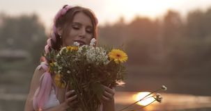 Woman in white dress smelling beautiful bouquet of flowers stock footage