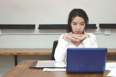 Front view of attractive young Asian business woman using laptop computer on the desk in office. Front view of attractive young Asian business woman using Royalty Free Stock Photo