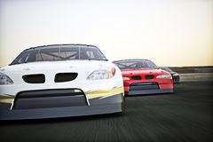 Front view of auto racing race cars racing on a track with motion blur. Room for text or copy space Stock Photos