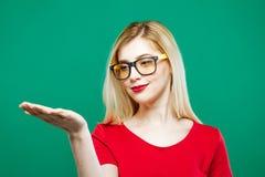Front View av den unga kvinnan med långt blont hår, glasögon och den röda överkanten som rymmer tomt utrymme på hennes hand på gr Fotografering för Bildbyråer