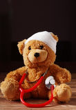 Front View of Bandaged Teddy Bear with Stethoscope Stock Image