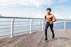 Front view of a bare chested man sprinting royalty free stock photography