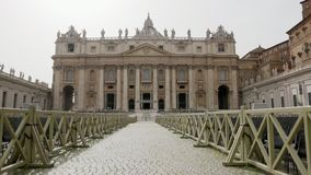 Front view of the Basilica of Saint Peter in Vatican City Italy with lots of chairs outside for people to listen to the. Mass, crane shot stock footage