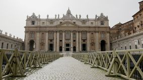 Front view of the Basilica of Saint Peter in Vatican City Italy with lots of chairs outside for people to listen to the. Mass, crane shot stock video footage