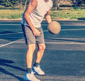 Front view of a basketball player holding a ball in a playground. Vintage tone effect stock photos
