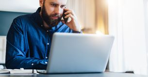 Front view.Bearded businessman is sitting at table in front of computer, talking on cell phone. Freelancer works at home. Front view. Young bearded businessman Stock Photography