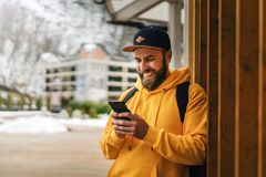 Front view. Bearded male tourist in yellow hoodie and cap with black backpack stands outdoors and using smartphone. Lifestyle royalty free stock photo