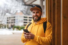Front view. Bearded male tourist in yellow hoodie and cap with black backpack stands outdoors and using smartphone. Lifestyle royalty free stock image