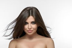 Front view of beatiful brunette looking at camera on white background. Front view of beatiful brunette with dispersing on wind hair looking at camera on white stock photography
