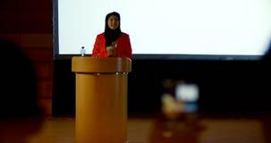 Mature Caucasian hijab businesswoman speaking at podium in auditorium 4k