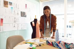 Female fashion designer looking at camera while working on table in a modern office. Front view of beautiful mixed race female fashion designer looking at camera stock photography