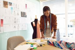 Female fashion designer looking at sketches on table in a modern office. Front view of beautiful mixed race female fashion designer looking at sketches on table royalty free stock photography
