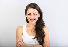 Front view of beautiful woman with nude makeup and healthy shine skin looking with folded arms. In casual clothing on light blue background with empty copy royalty free stock photography