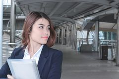 Front view of beautiful young Asian business woman holding ring binder and looking at far away at walkway outside office with copy Royalty Free Stock Images