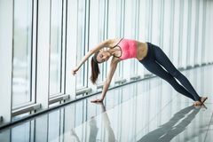 Front view of beautiful young woman in sportswear doing stretching while sitting on the floor in front of window at gym. Dedicated to fitness. Front view of Stock Images