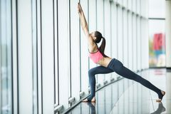Front view of beautiful young woman in sportswear doing stretching while sitting on the floor in front of window at gym Stock Images