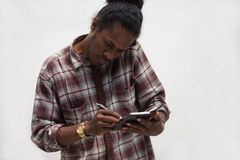 Close up front view of black man taking notes while talking on phones, young papua man talk with smartphone while write on notes. Front view of black man taking royalty free stock photography