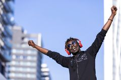 Front view of a black man wearing casual clothes and sunglasses standing in the street while using headphones to listen music in stock photos