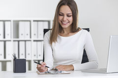 Front view of blond woman writing in clipboard Stock Photo