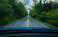 Front view of blue car driving with fast speed on the middle of asphalt road with white and yellow line of traffic symbol royalty free stock images