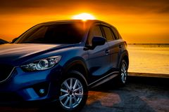 Front view blue compact SUV car with sport and modern design parked on concrete road by the sea at sunset. Electric car technology royalty free stock photo