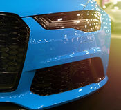 Front view of blue modern luxury sport with soft orange sun light. Car exterior details. Headlight of a modern sport car. The front lights of the car stock image