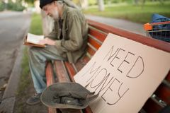 On front view board with sign need money and hat with some coins, reading tramp on backdrop. Life of an old beggar living in the streets Stock Photography