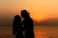 Front view of a body of a couple silhouette. On the beach at sunset in summer Stock Image
